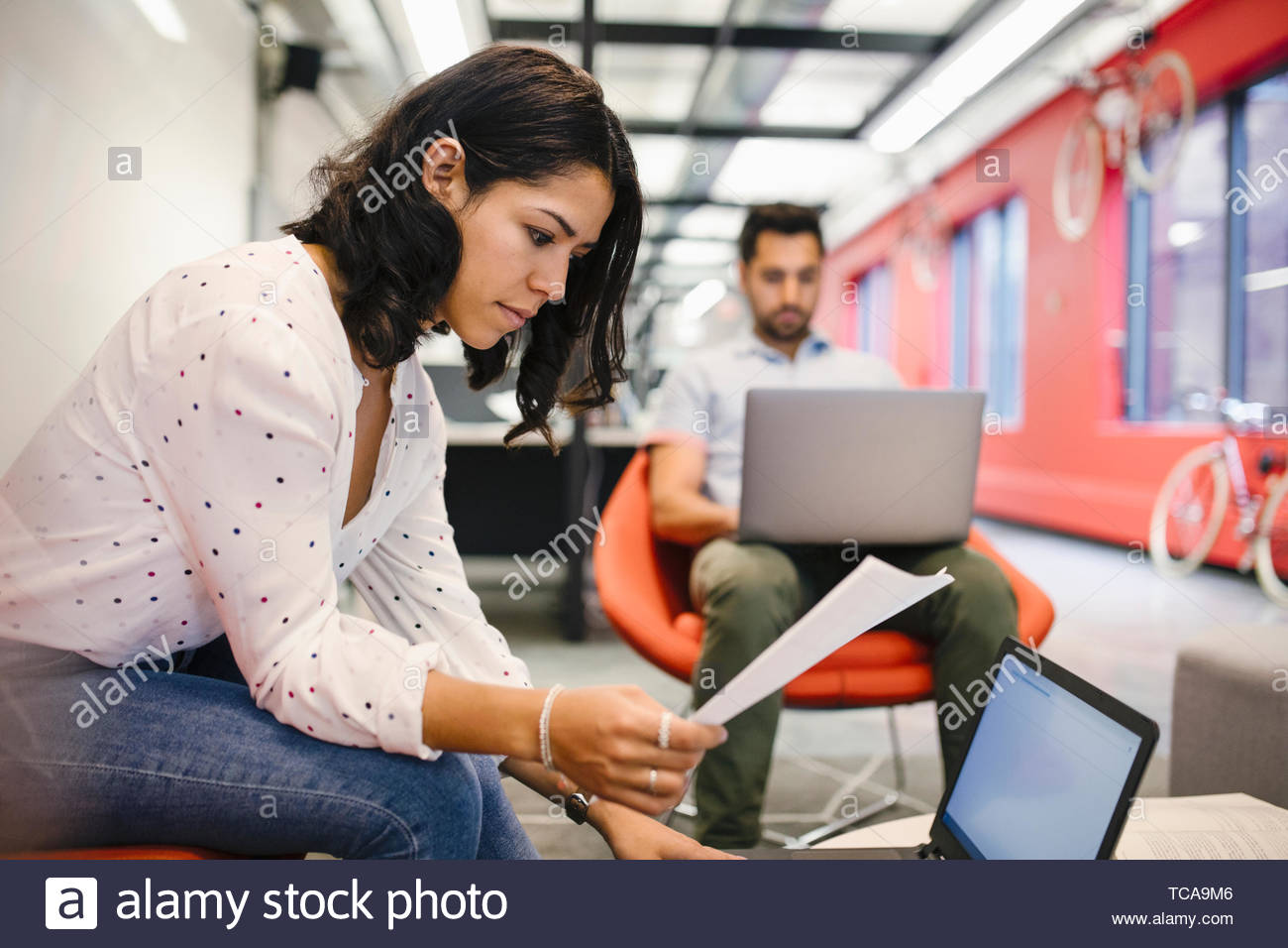 L'accent businesswoman with paperwork working at laptop Photo Stock