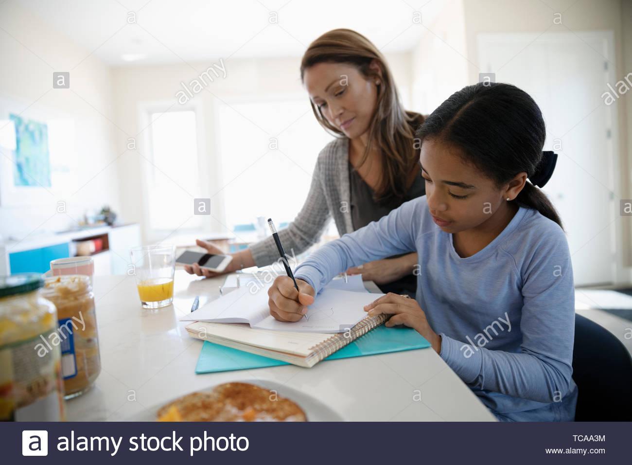 Mère fille aidant à faire leurs devoirs dans la cuisine Banque D'Images