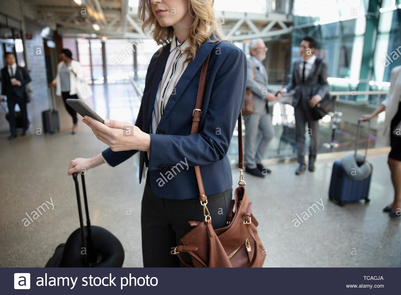 Businesswoman with suitcase using smart phone in airport Photo Stock