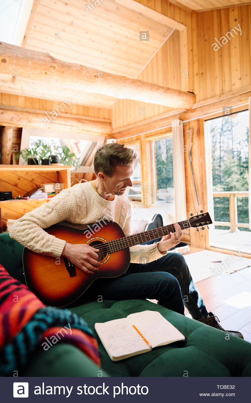 Man with guitar song writing dans la cabine Photo Stock