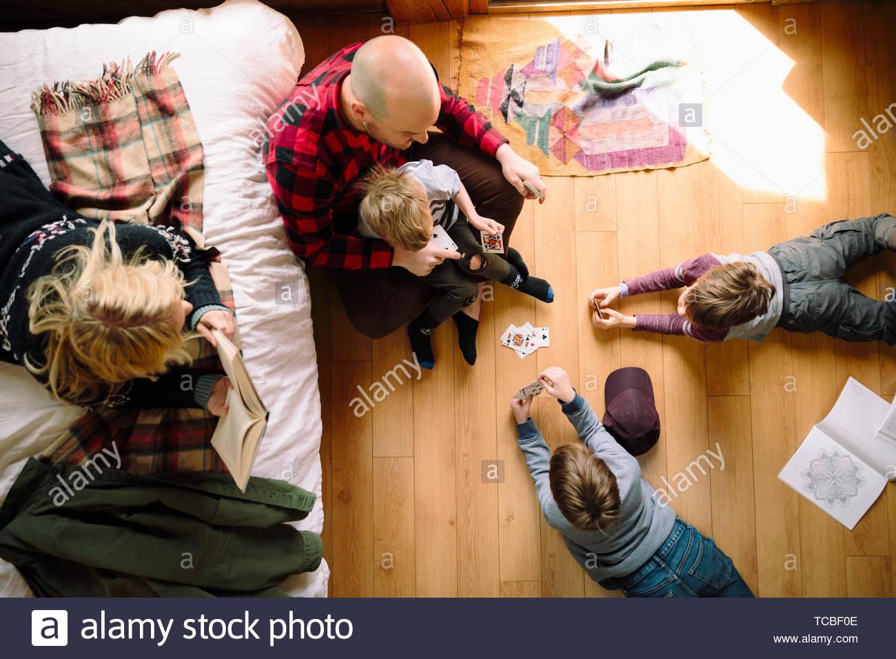 Vue du dessus, la lecture de détente de la famille et de cartes à jouer dans la cabine Photo Stock