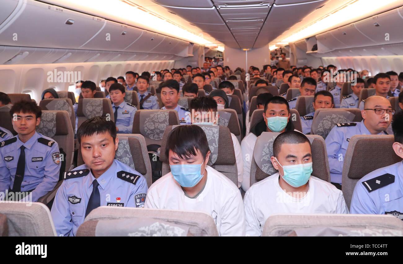 Beijing, Chine. 7 juin, 2019. L'escorte de police suspects dans un avion pour Pékin le 7 juin 2019. Un groupe de 94 suspects, escorté par la police chinoise, ont été transportés à Beijing de l'Espagne vendredi matin, la première livraison de suspects de fraude télécom chinois sur cette échelle de l'Europe. Credit: Yin Gang/Xinhua/Alamy Live News Photo Stock