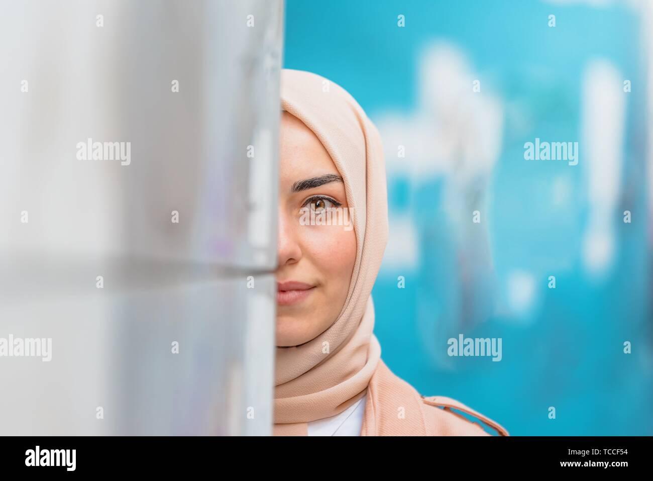 Belle femme musulmane en foulard et des vêtements modernes à la mode se cache la moitié de visage au mur avec fond bleu. Banque D'Images
