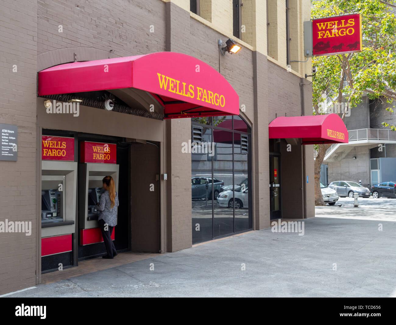 Femme à l'aide de la Wells Fargo distributeur de billets à l'extérieur de l'emplacement de la direction générale Banque D'Images