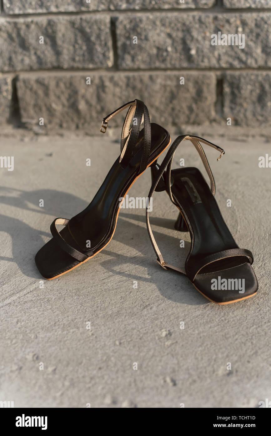 Sandales ouvertes en cuir noir avec stand talons sur l'asphalte dans le soleil. Chaussures pour femmes avec boucles sans que personne. Photo verticale d'élégant et fashio Photo Stock
