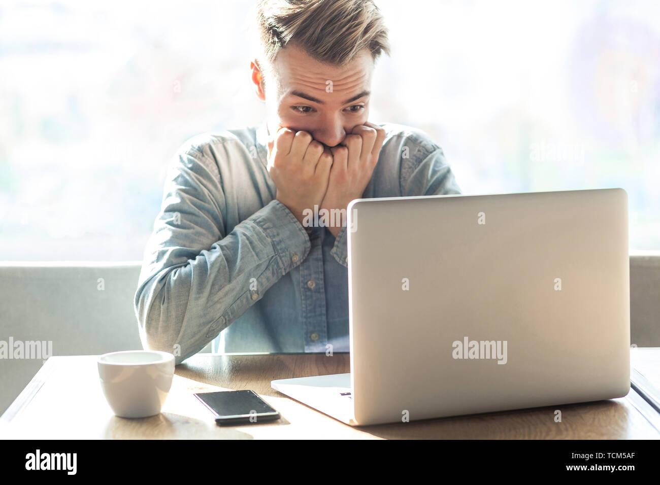 Effrayé ou nerveux! Portrait of young businessman nerveux émotionnel en chemise bleue sont assis dans le café en ligne de travail et de mordre d'ongle lui-même cause faite Banque D'Images