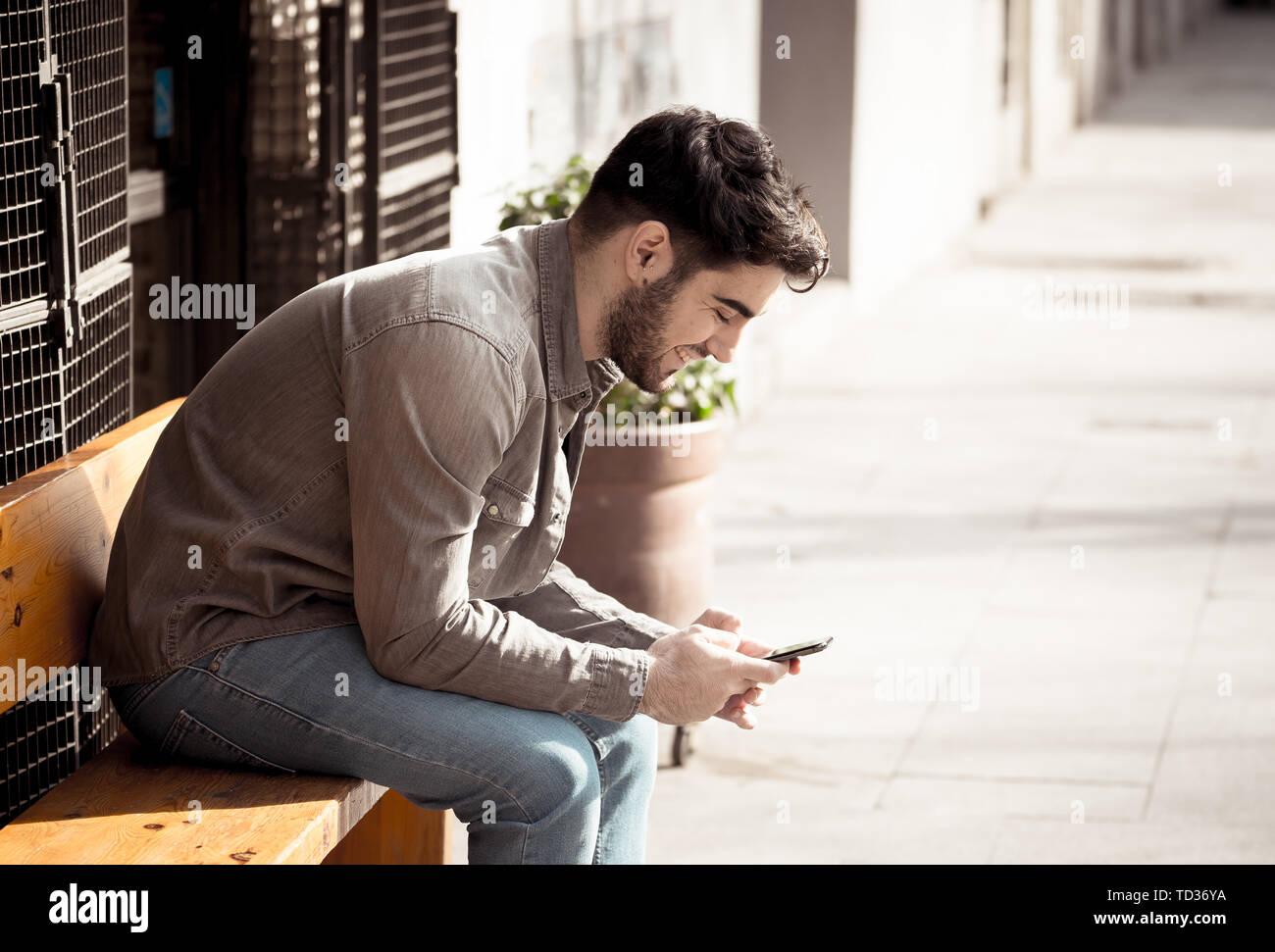 Collège de la mode homme d'une vingtaine d'heureux blog contrôle et de chatter sur internet avec des amis sur smart mobile phone app en plein air européen ville. Banque D'Images