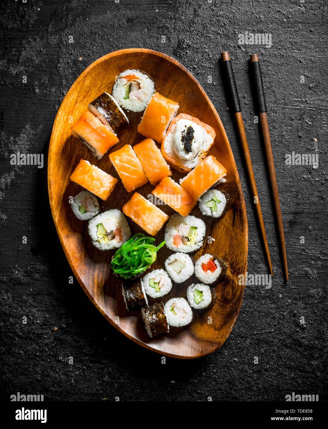 Différents rouleaux de sushi avec le saumon et les légumes sur une plaque de bois avec des baguettes. Noir sur fond rustique Banque D'Images