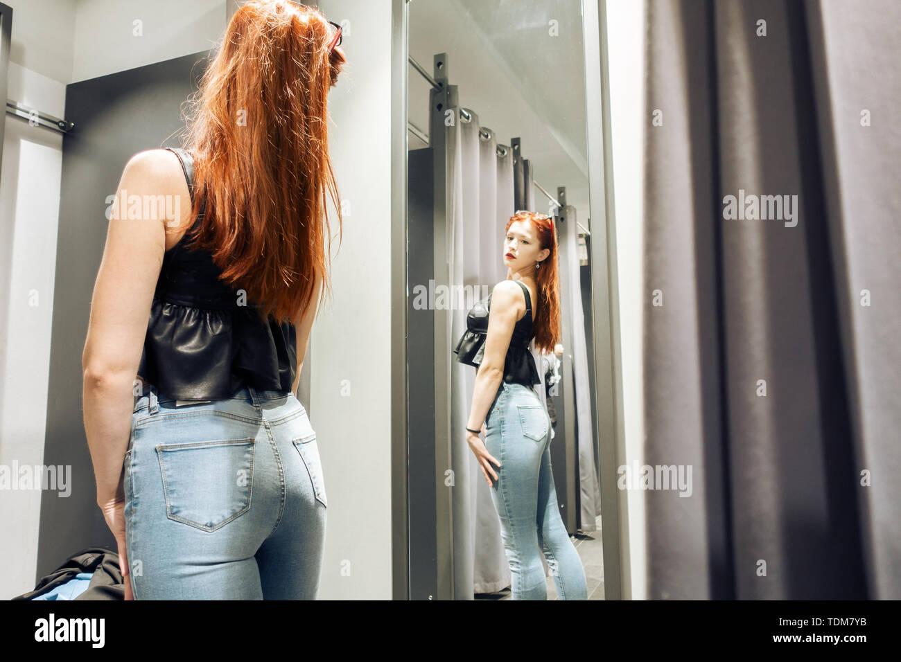 e147064530e4e Jeune fille slim essayant sur nouveau jean dans le salon d'essayage dans le  magasin