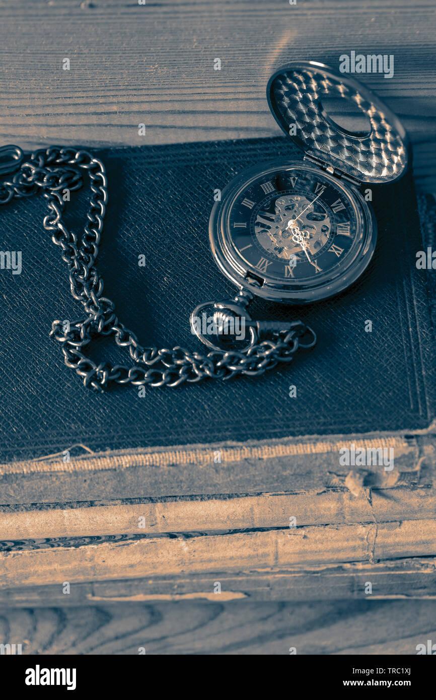 Fob watch poche antique avec une chaîne sur une pile de vieux livres. Sur un fond de bois avec l'harmonisation des couleurs. Photo Stock