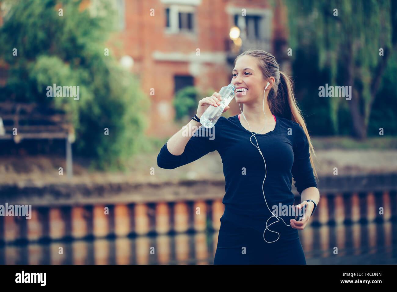 Coureuse debout près de la rivière tenant une bouteille d'eau. Femme de remise en forme en faisant une pause après l'exécution de l'entraînement. Banque D'Images