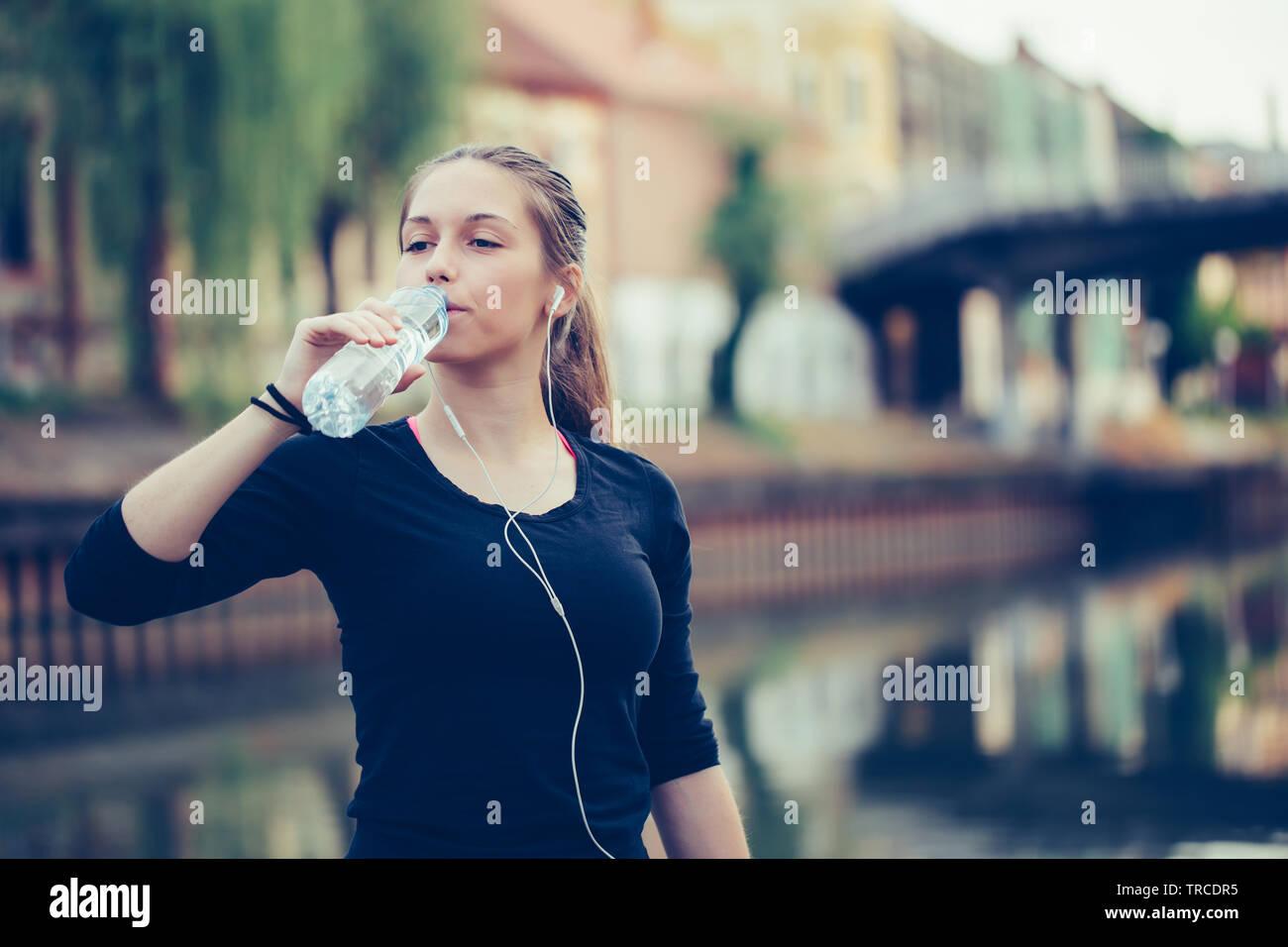 Belle femme athlète remise en forme de l'eau potable après l'exercice d'entraînement. Banque D'Images