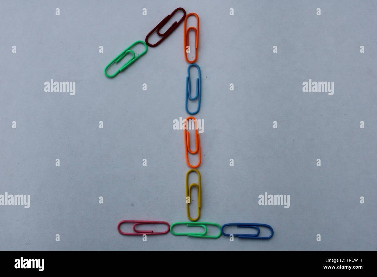 Numéro 1 fait avec des trombones colorés sur fond blanc Photo Stock
