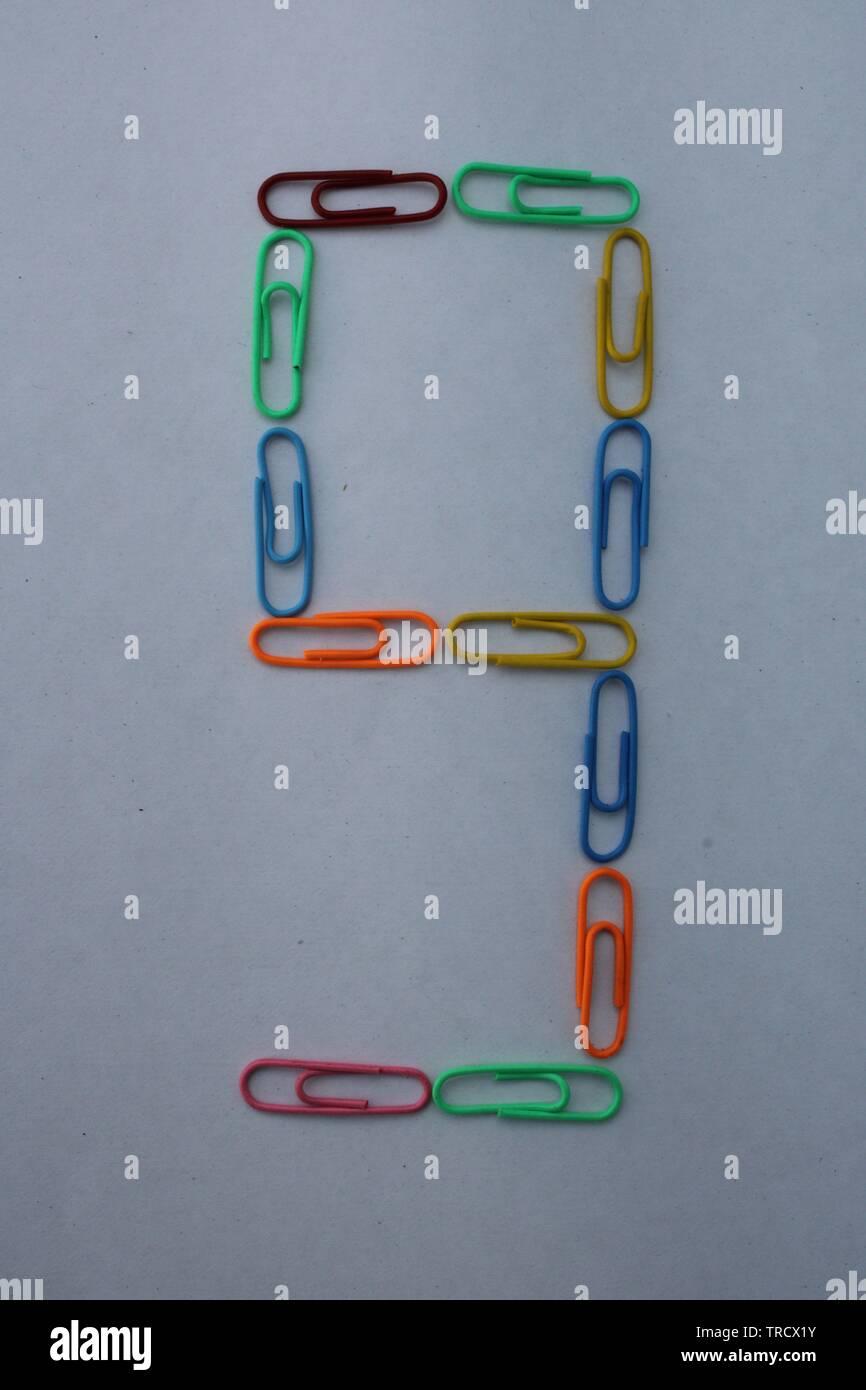 Numéro neuf fait avec des trombones colorés sur fond blanc Photo Stock