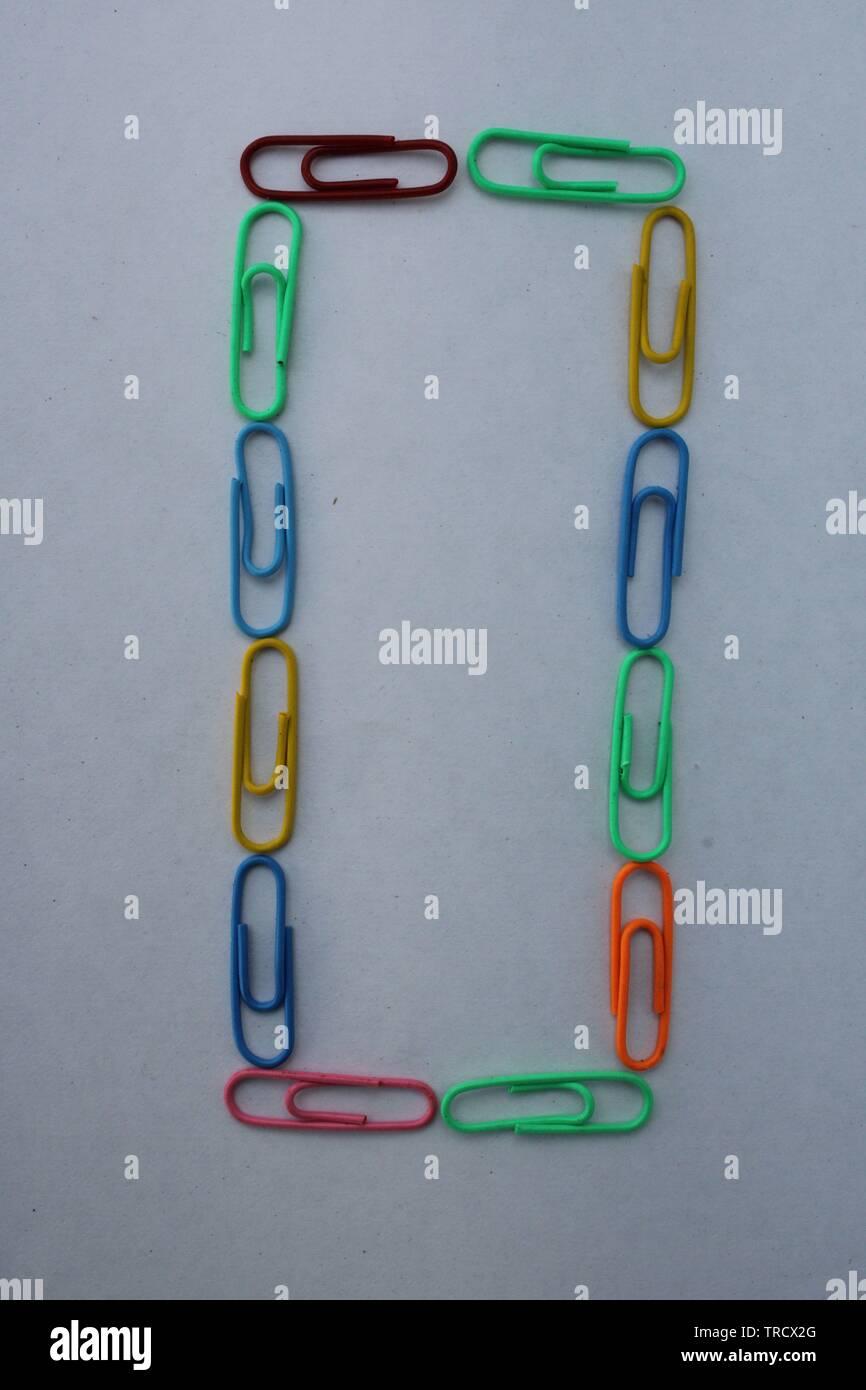Numéro 0 fait avec des trombones colorés sur fond blanc Photo Stock