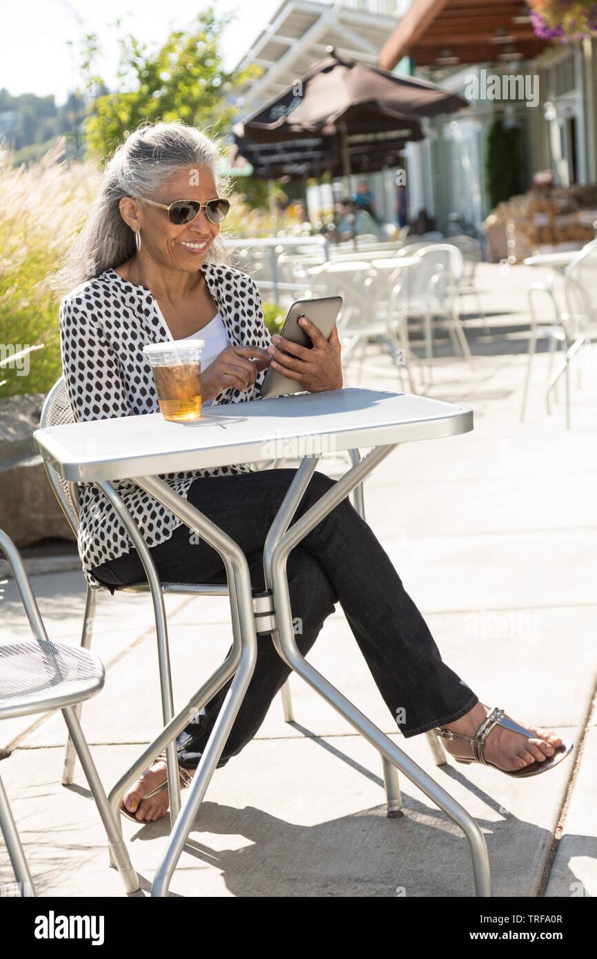 Heureux, mature, black, African American Woman with digital tablet e-reader au café en plein air. Les personnes d'âge moyen à l'aide de la technologie mobile personnelle. Photo Stock
