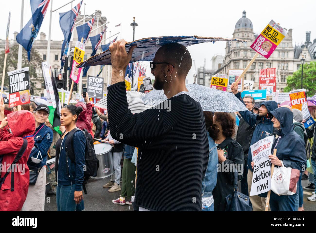 4 juin 2019. Londres, Royaume-Uni. Trump anti rassemblement à Westminster. Un protestataire se cache de la pluie sous la plaque. Banque D'Images
