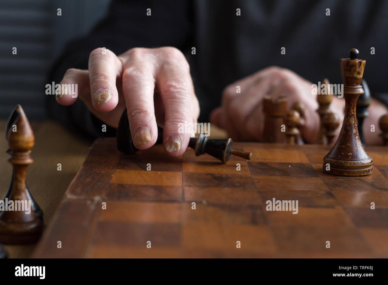 La main d'un vieil homme met une figure du roi noir sur le conseil reconnaissant la perte, jeux d'entreprise concept, selective focus, copyspace Banque D'Images