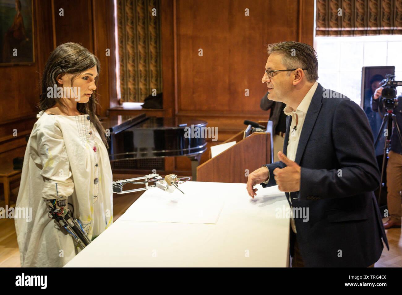 Oxford, UK. 5 juin, 2019. Le premier artiste robotique est dévoilé à Lady Margaret Hall, à Oxford. Le robot, appelé Ai-Da après Ada Lovelace qui a été la première femme programmeur informatique, l'invention d'Aidan Meller (en photo avec Ai-Da) qui gère les galeries à Londres et Oxford. L'IA utilise des algorithmes personnalisés pour analyser les visages humains et d'autres scènes et créer des pièces artistiques fondées sur ces derniers. Le croquis au crayon que le robot crée sont alors transformées en peintures complète par l'application de peinture par les assistants. Crédit: Andrew Walmsley/Alamy Live News Photo Stock