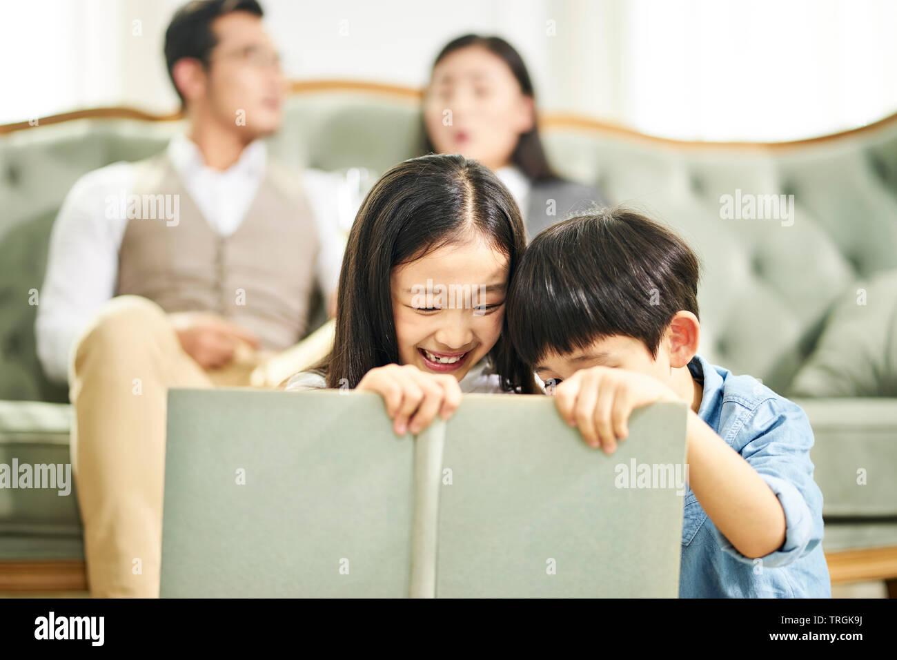 Deux enfants frère et sœur asiatique assis sur un tapis lecture livre ensemble en famille séjour avec les parents assis sur le canapé dans l'arrière-plan. Banque D'Images