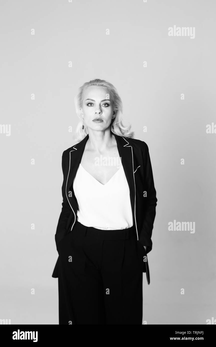Portrait de studio de belle blonde woman in a black dress contre fond uni blanc Photo Stock