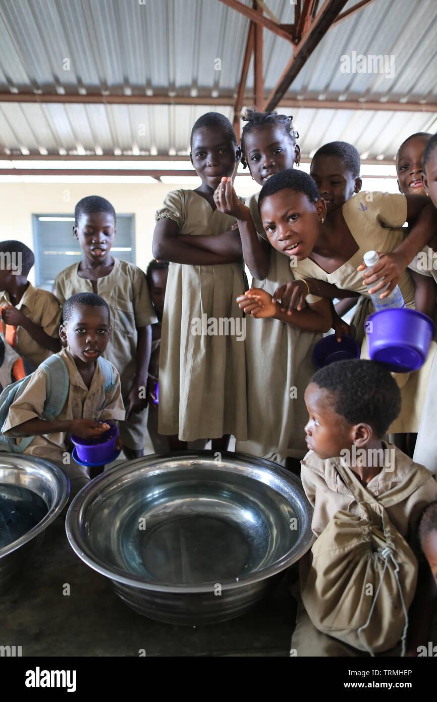 La distribution de l'eau pour la vaisselle. Ecole primaire. Lomé. Le Togo. Afrique de l'Ouest. Photo Stock