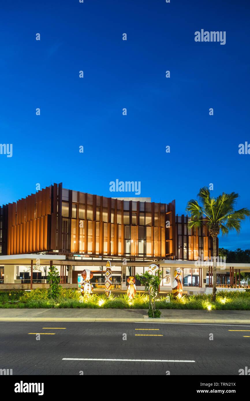 """La façade de la Performing Arts Centre de Cairns allumé au crépuscule. Un ensemble de """"Bagu' les sculptures s'asseoir à l'avant du centre. Cairn Banque D'Images"""