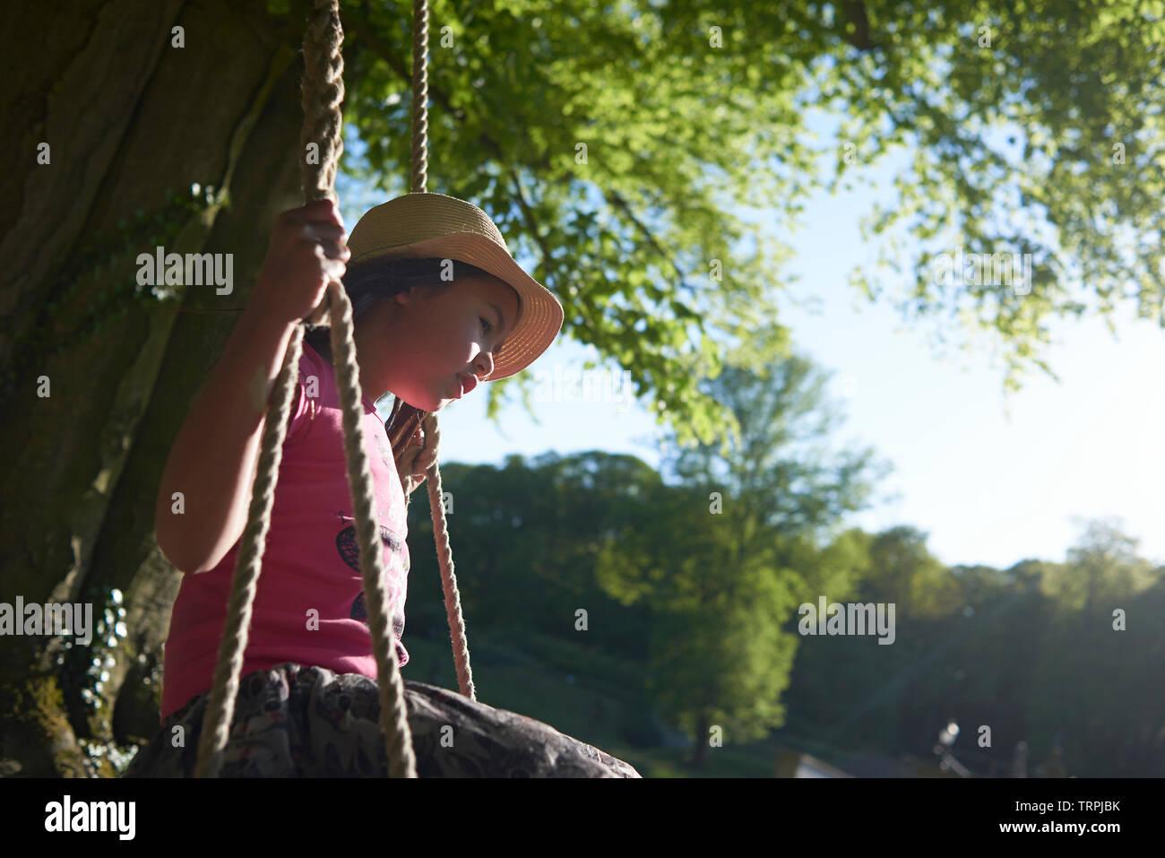 Mère de l'Asie et sa jeune fille s'amusant à jouer sur une balançoire accrochée à un gros arbre en face d'un château en plein soleil d'été Banque D'Images
