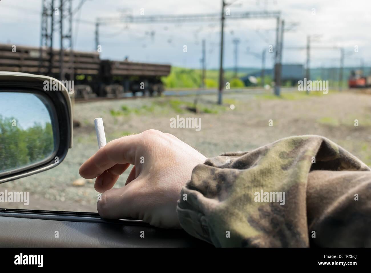 Les hommes de main, militaire, en vêtement de camouflage, tenant une cigarette tandis que dans la voiture, qui est près du passage à niveau avec des wagons de marchandises Photo Stock