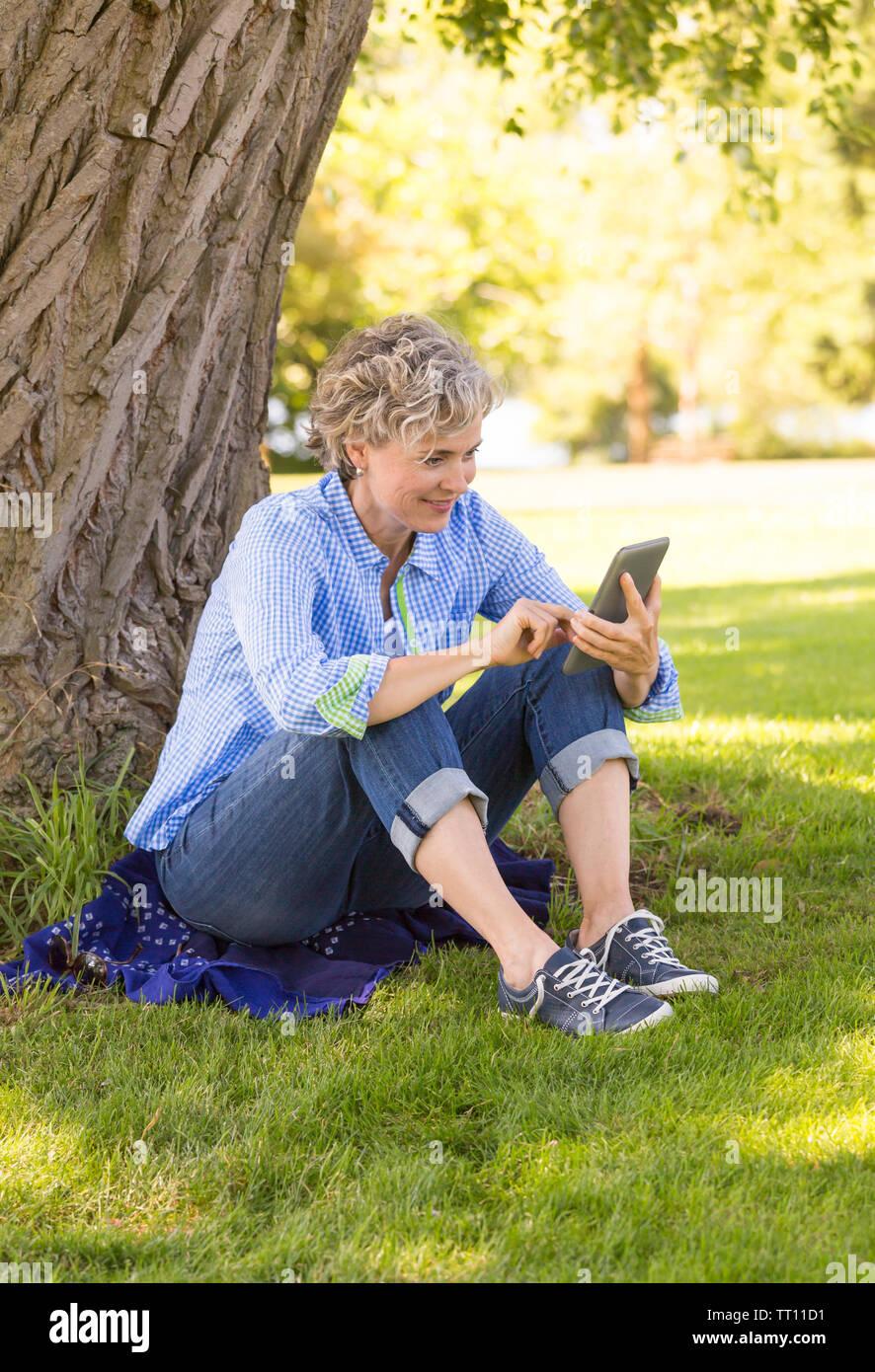Heureux, souriant, middle aged woman using a digital tablet computer e-reader à l'extérieur dans un parc. Elle est en contact avec l'écran. Photo Stock