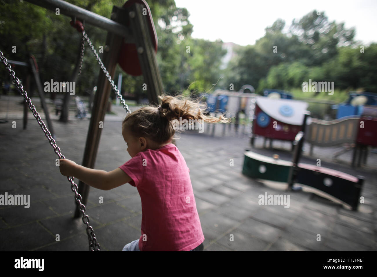 Jeune fille se balançant dans une aire de jeu pour les enfants sans que personne autour. Photo Stock