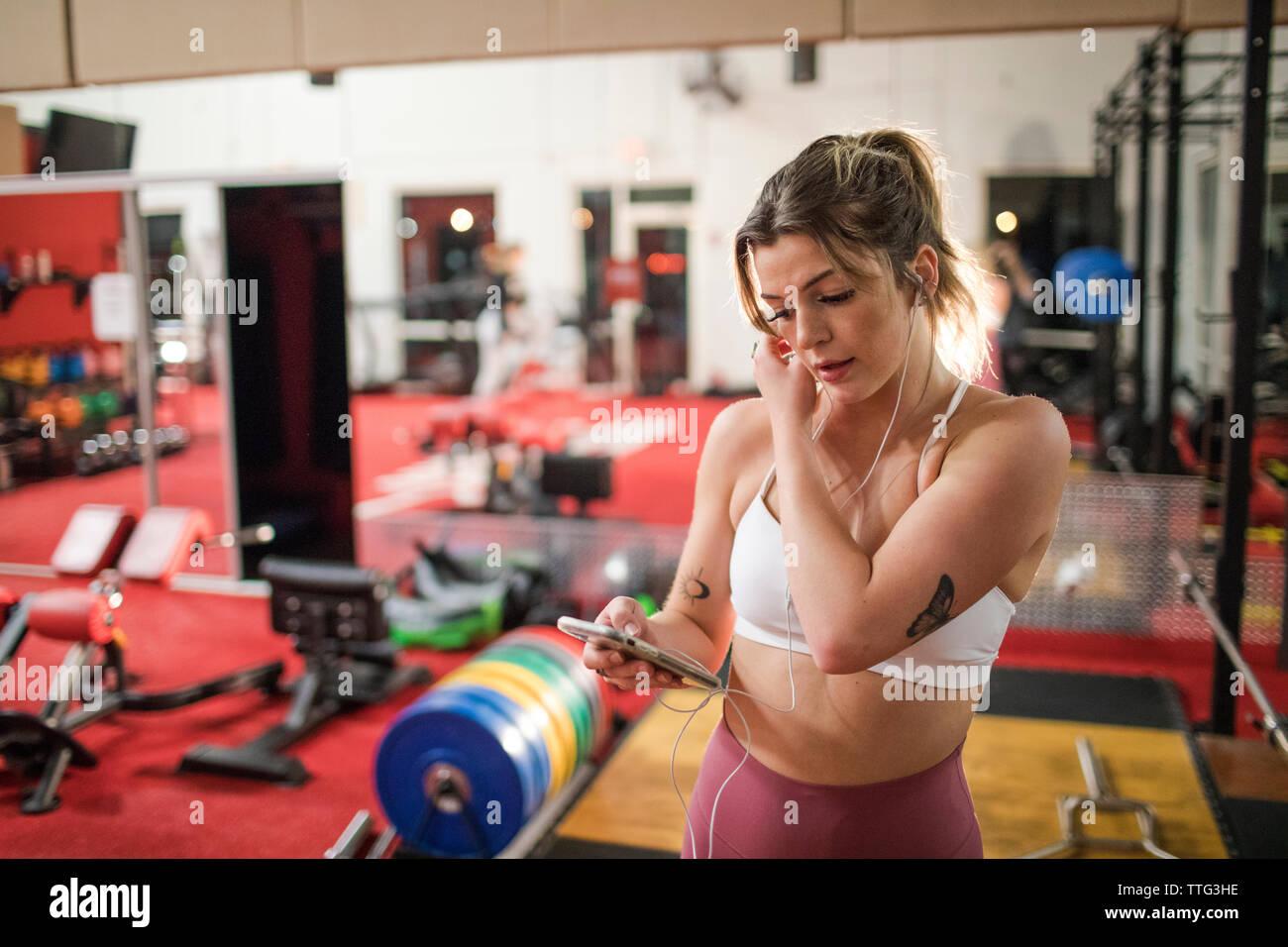 Jeune femme à l'écoute de la musique avec vos écouteurs et smartphone at gym Banque D'Images
