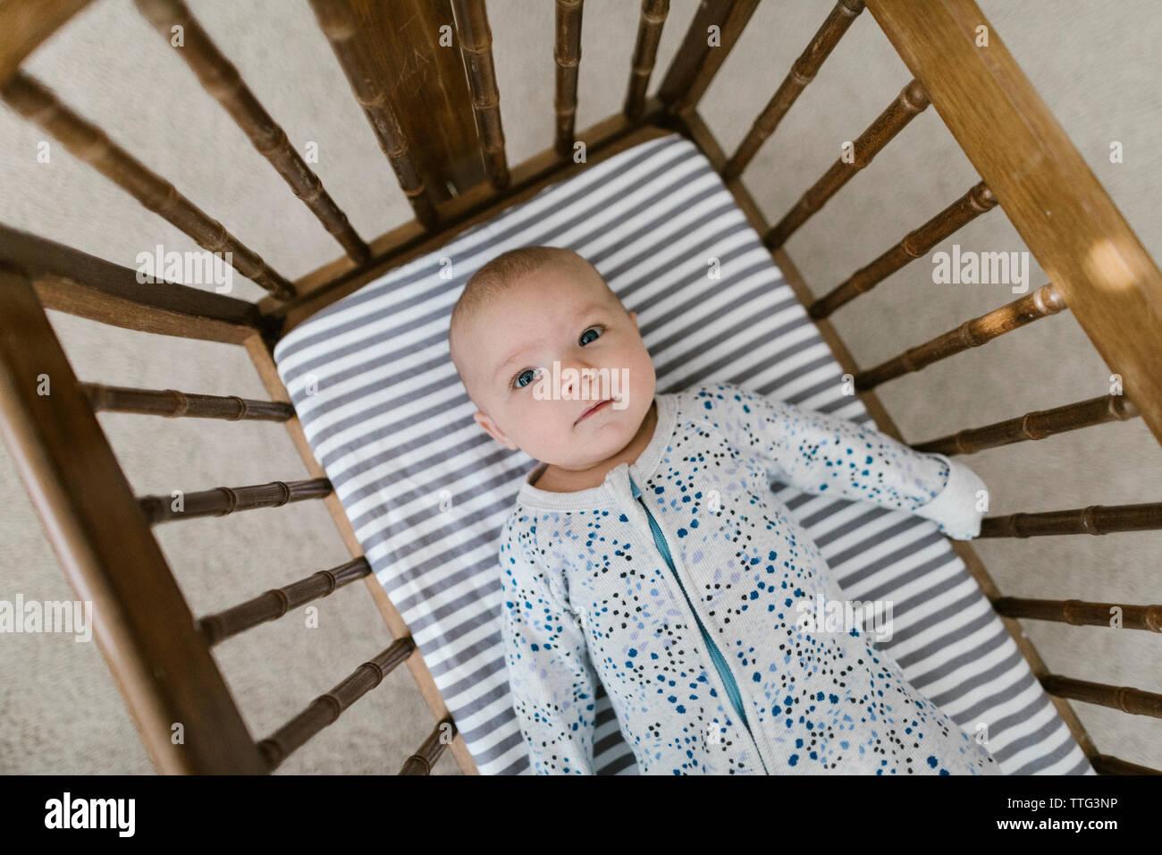 Vue de dessus de la pose bébé dans un berceau en bois Banque D'Images