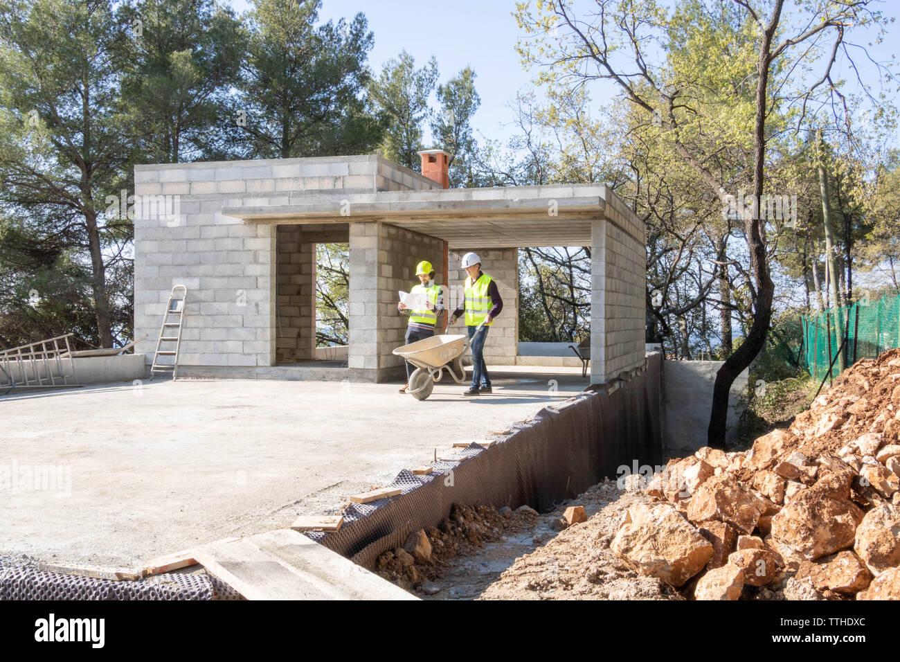Chef de site donnant des instructions d'un maçon sur le chantier de construction d'une maison en construction Banque D'Images