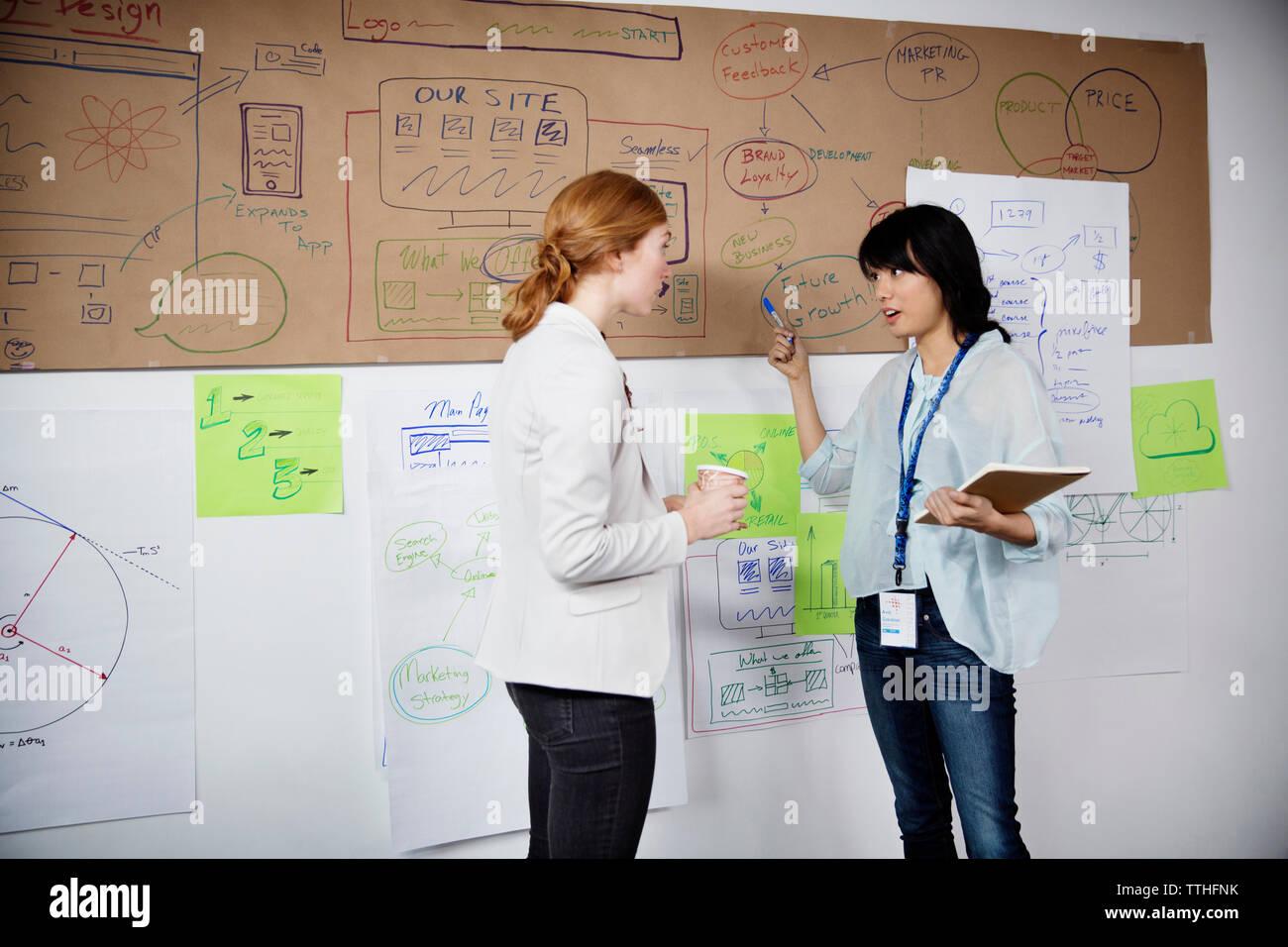 Plus de Businesswomen discussing charts alors que standing in office Banque D'Images