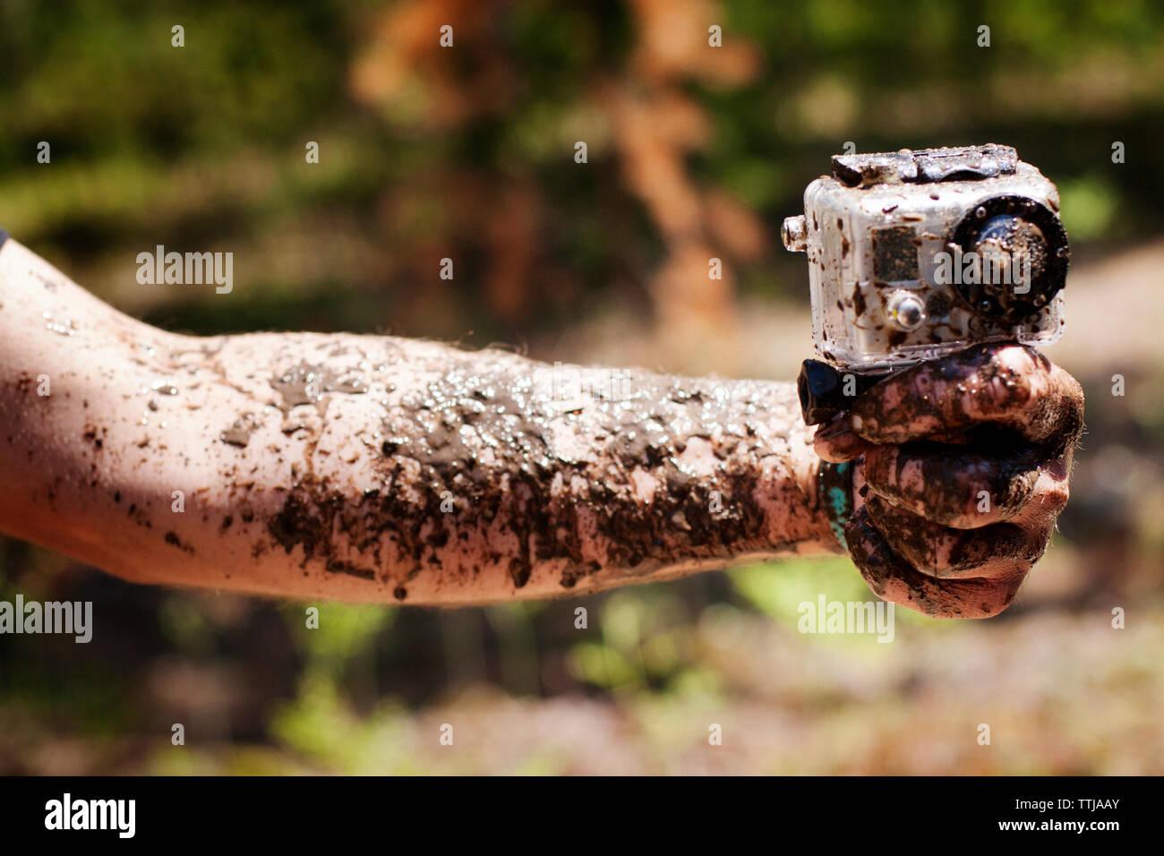 Portrait de main boueuse holding camera Banque D'Images
