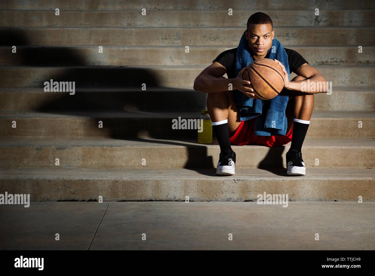 Portrait d'athlète avec le basket-ball sitting on steps Banque D'Images