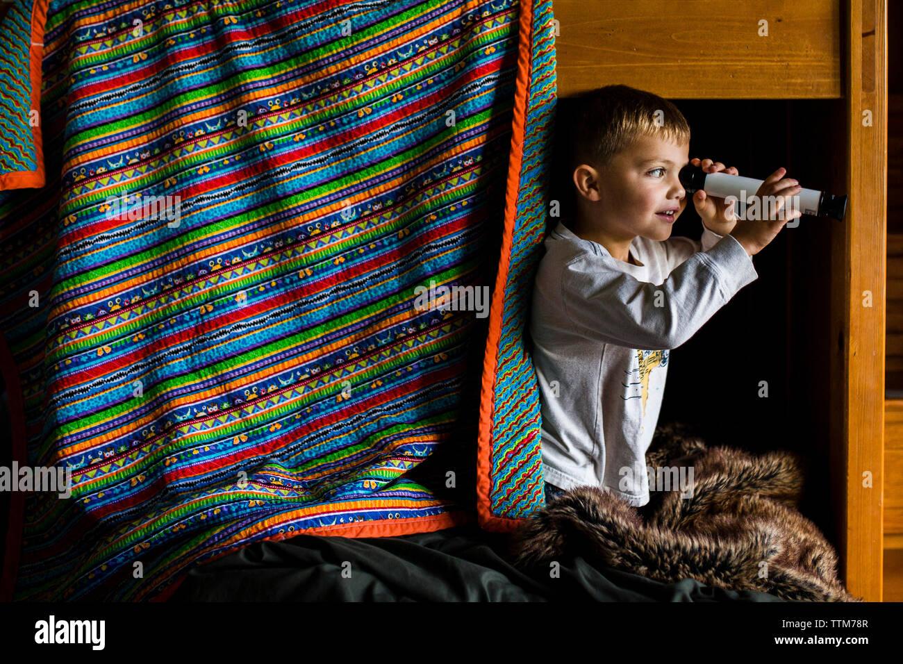 Curieux boy looking through telescope en se tenant sur le lit superposé Photo Stock