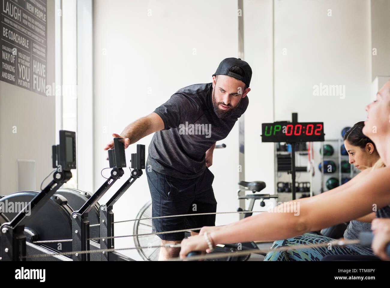 Contrôle de l'instructeur d'une machine à ramer pendant que les femmes dans l'exercice de gym crossfit Photo Stock