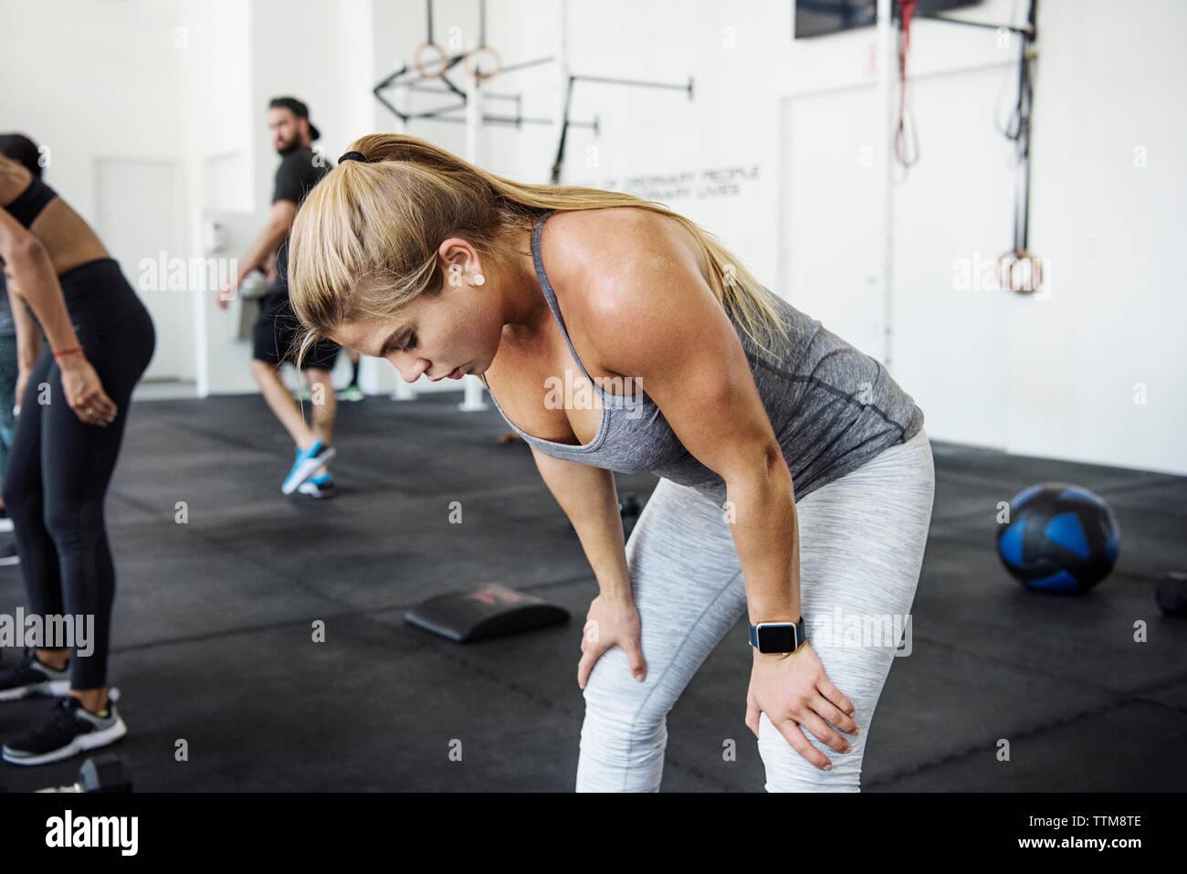 Athlète féminine fatigués se détendre après cross insérer la formation en salle de sport crossfit Photo Stock