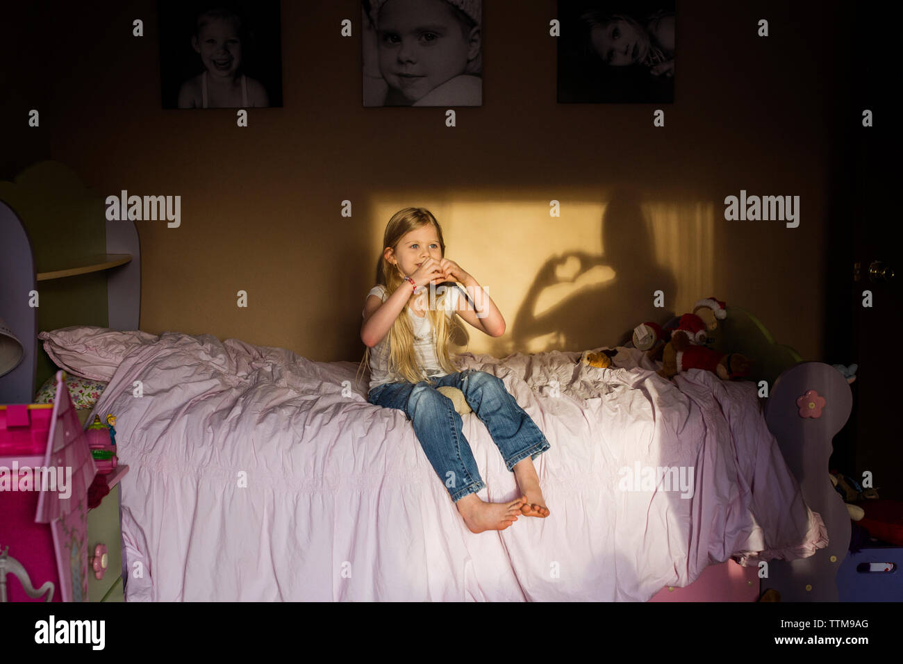Girl making heart shape with hands while sitting on bed at home Banque D'Images