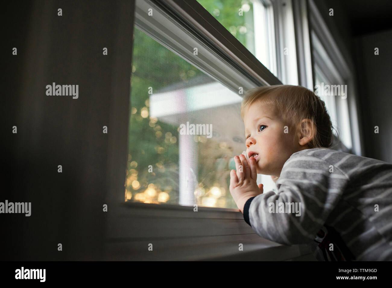 Low angle view of curieux garçon à la recherche d'une fenêtre Photo Stock