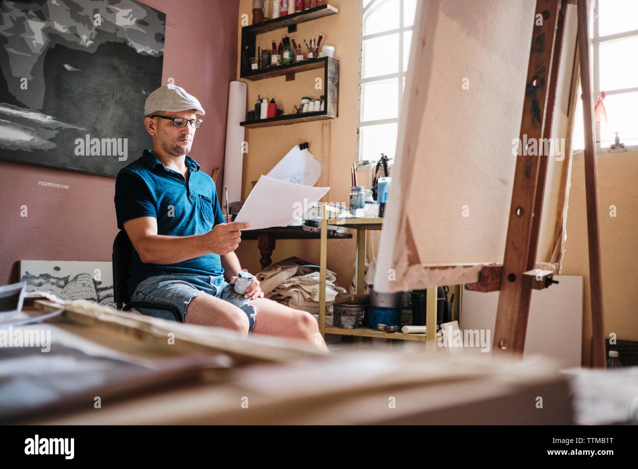 L'homme travaillant comme peintre à la recherche à l'image de référence pour la nouvelle peinture Banque D'Images