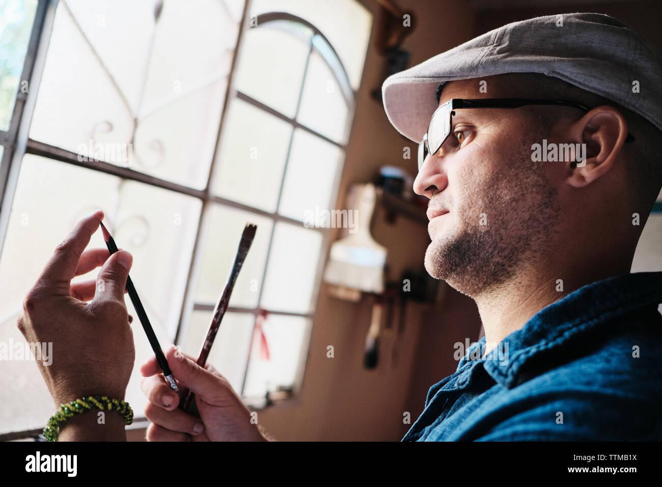 L'homme travaillant comme peintre contrôle brosse et embout de crayon avant peinture Banque D'Images