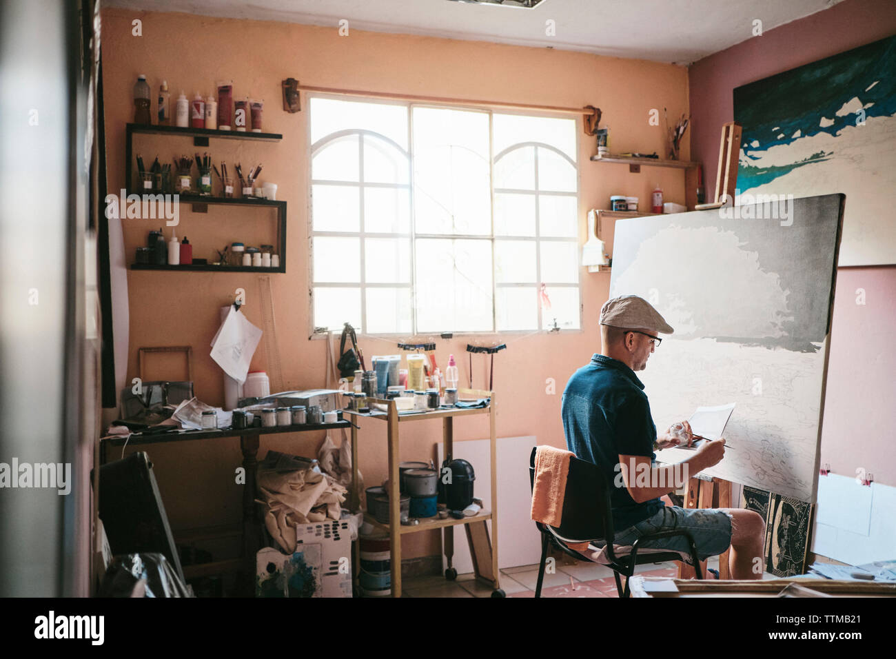 Mid adult man travaillant comme peintre avec un pinceau et de la toile dans son atelier Banque D'Images