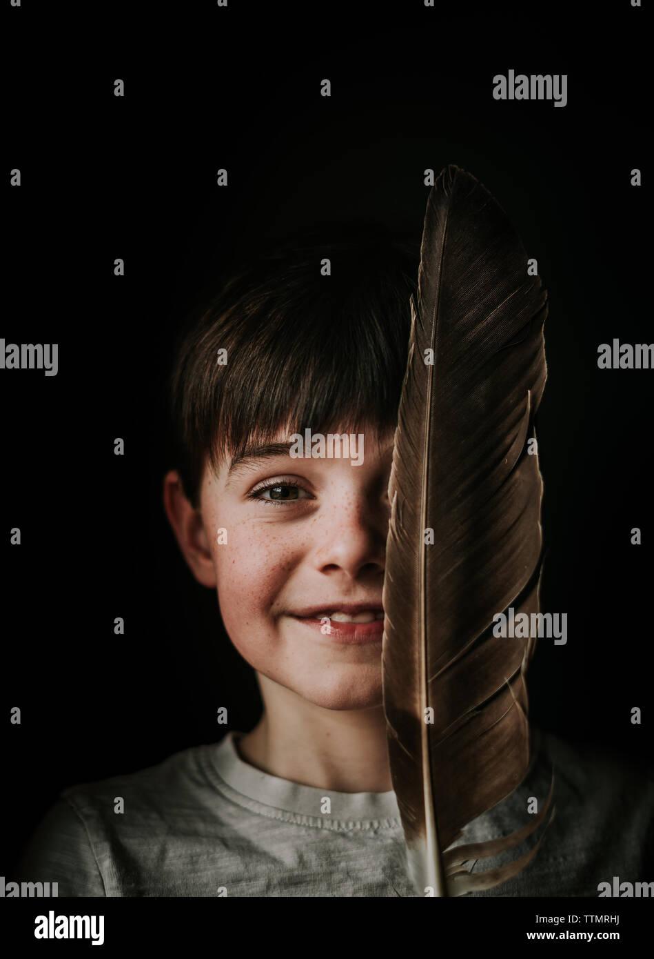 Portrait de jeune garçon tenant un grand feather plus de la moitié de son visage. Banque D'Images