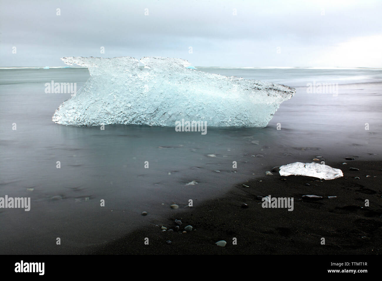 Berg de glace en mer contre ciel nuageux Photo Stock