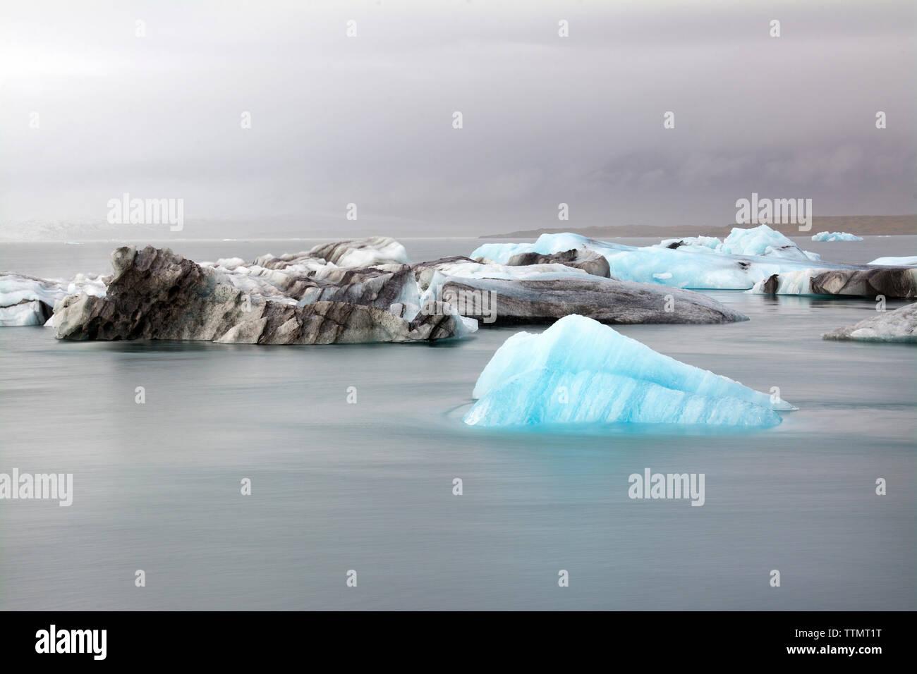 Les glaciers en mer contre ciel nuageux Photo Stock