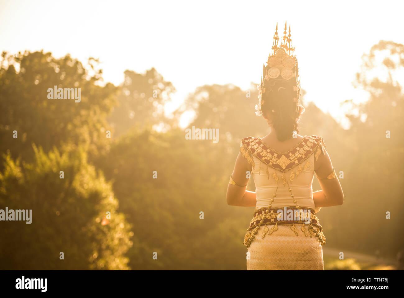 Vue arrière de la femme dans les vêtements traditionnels contre des arbres debout Photo Stock