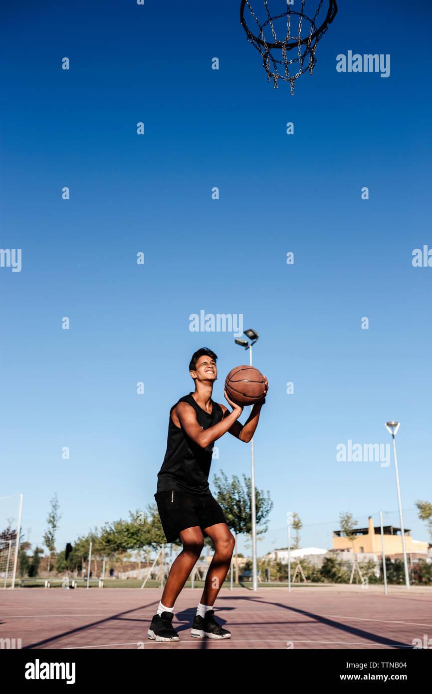 Toute la longueur de teenage boy throwing ball en basket-ball contre un ciel clair à la cour Banque D'Images